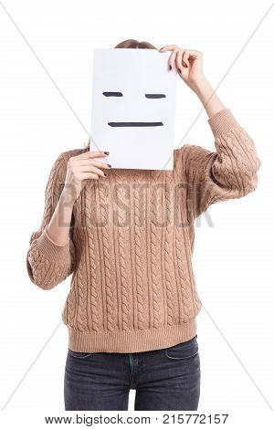 A girl in a beige sweater and jeans covers her face with a smiley face sheet with a poker face on a white isolated background