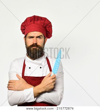 Cook With Serious Face In Burgundy Apron And Chef Hat.