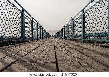 Silhouette of a man on a pedestrian bridge over the railway. Pedestrian bridge. Bridge. Wooden bridge.