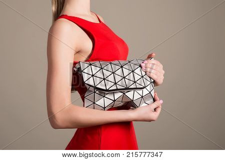 Attractive Slim Girl In A Red Evening Dress Holds A Stylish Bag Of Silvery Triangles