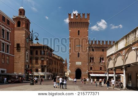 FERRARA, ITALY - JUNE 17, 2017: People walking on Piazza Trento against the Ferrara Town Hall. Begun in 1245, the City Hall was the residence of the Este family until the 16th century
