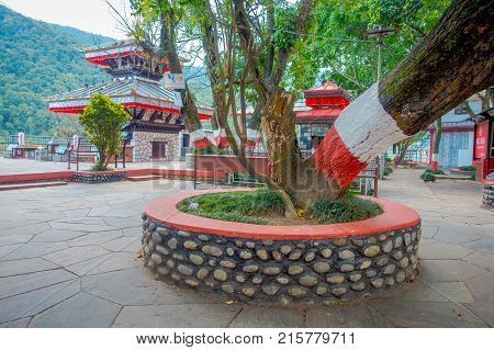 POKHARA, NEPAL - SEPTEMBER 04, 2017: Public jarden with a huge tree close to Tal Barahi Temple, located at the center of Phewa Lake, is the most important religious monument of Pokhara.