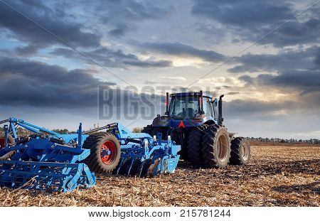 Tractor working on the farm, a modern agricultural transport,  fertile land tractor on a sunset background, cultivation of land agricultural machine