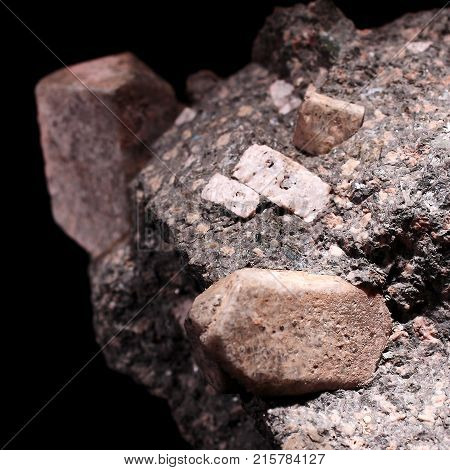 Closeup photograph of several rhyodacite stones and black background, . Natural phenomenon.