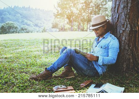 Asian man relax in the holiday. Study read a book. Read a book In the garden on the Moutain. In Thailand