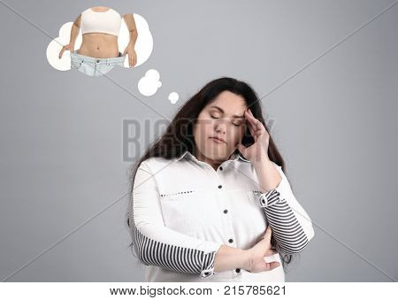Overweight woman dreaming about slim body on grey background. Weight loss concept