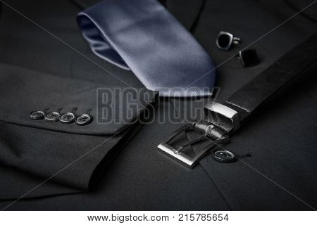Elegant tie, cuff links and belt on male jacket, closeup