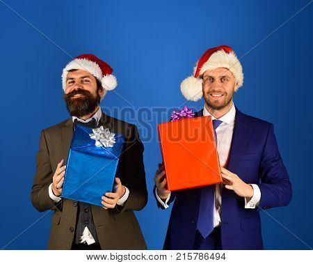 Men In Smart Suits And Santa Hats On Blue Background.