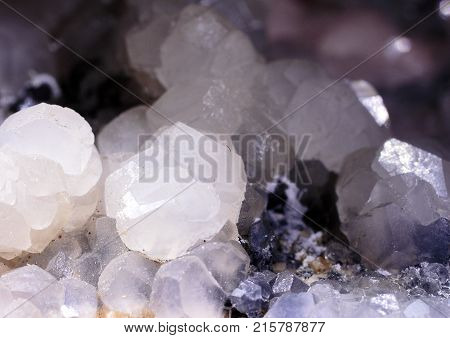 Closeup photograph of glittering translucent calcite stone crystal with white, purple and black details. Natural phenomenon.