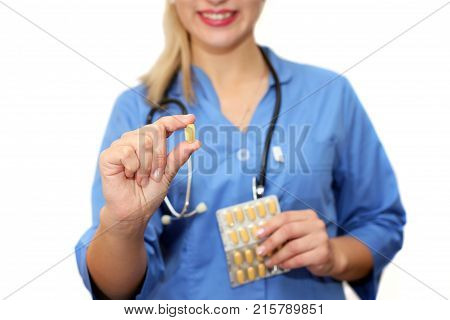Woman doctor holding a capsule tablet isolated on a white background