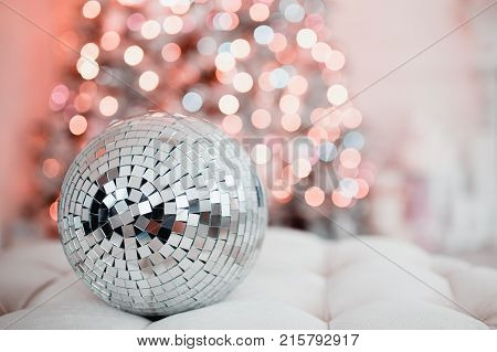 Disco ball. Close-up of a mirror ball against the backdrop of a Christmas tree and garland lights. Concept Christmas party.