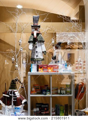 STRASBOURG FRANCE - NOV 21 2017: Cough cold and flu medication and vitamines on display of a winter-theme and Christmas decorated pharmacy store window