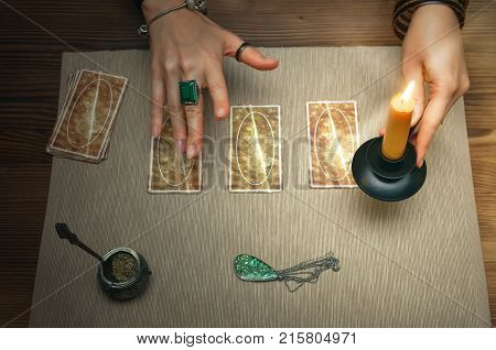 Tarot cards on fortune teller desk table. Future reading. Woman witch holds in her hands a burning candle.