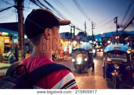 Young man walking on the busy street full of shops - Chiang Mai Thailand