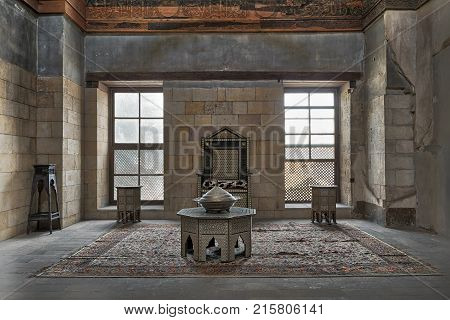 Cairo Egypt - November 25 2017: Hall at the palace of Prince Taz with stone bricks wall decorated by calligraphy with two windows historic chair and tables Old Cairo