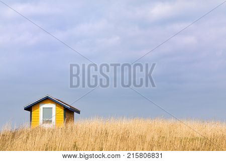 Small yellow hut in long grass in Havre Aubert, Iles de la Madeleine, Canada. Big, gentl sky with space for your text