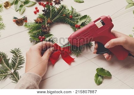Creative leisure, tools and trinkets for xmas holiday decoration. Point of view of white wooden table background with woman hands with glue gun making wreath
