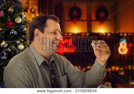 Smiling mature man makes a toast for Christmas Eve. Side portrait of friendly man holding vodka shot. He sits in a cafe on holiday blurred background