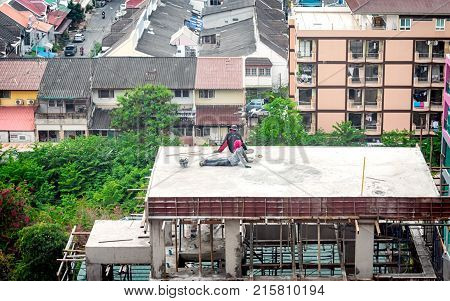 PATTAYA THAILAND - NOVEMBER 21: Construction workers takes a break on the roof of a tall buiding under construction in Pattaya on November 21 2017.