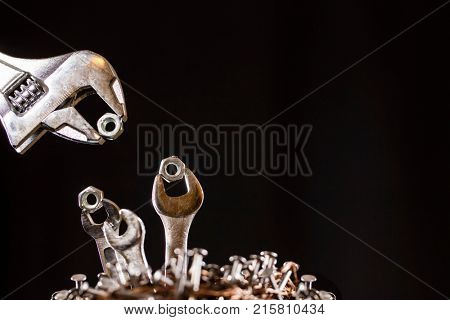 Conception of an adjustable wrench feeding baby wrenches in a nest of nails