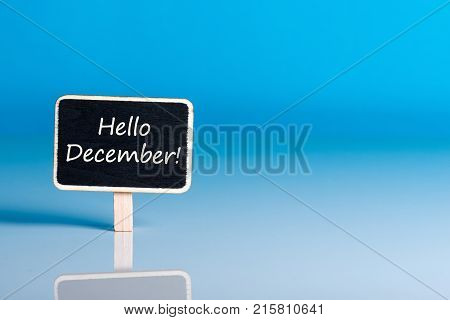 Hello december on sign at blue background with empty space for text, mockup. December 1st, the beginning of the Christmas and New Year holidays and sales.