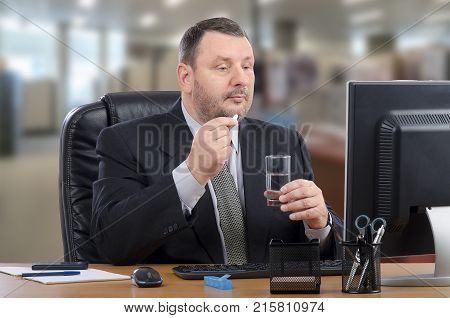 Businessman intends to swallow white pill during telehealth doctor appointment. Mature man in black suit sits at his office desk looking to computer monitor