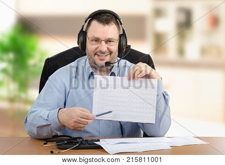 Positive virtual male doctor goes over printed heart-rate graph looking at the camera. Middle-aged man in headset wearing blue shirt sits at wooden office desk. Indoors blurred background