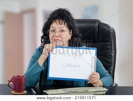 Psychologist is engaged in the use of distance counseling. Black-haired mature woman in glasses holds written message Forgive Others looking at the camera.