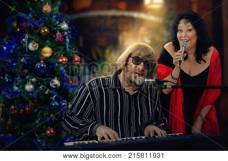 Man and woman sing duets at Christmas songs. Man in light yellow wig plays electric piano. Mature woman in big red scarf is singing nearby. Holiday indoors blurred background