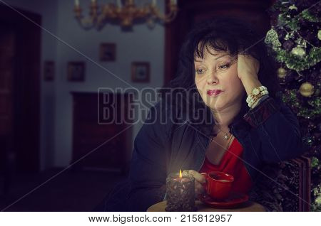 Mature woman is upset and frustrated about holiday. It's a hard time of Christmas to spend too much time alone. Black-haired woman drinks coffee head is propped up with her hand. Dark blurred indoors background