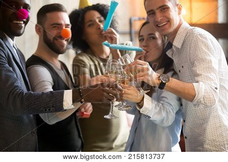 Multiracial young people in party hats clinking glasses celebrating New years day eve or birthday, diverse friends looking at camera having fun holding champagne, blowing whistles at celebration