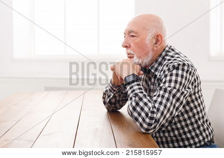 Pensive elderly man sitting at wooden table, copy space. Serious senior male with thoughtful facial expression