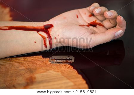 suicide, death and people concept - close up of dead woman hand in blood on floor at crime scene (staged photo)