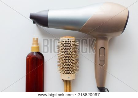 hair tools, beauty and hairdressing concept - hairdryer, brush and hot styling spay on white background