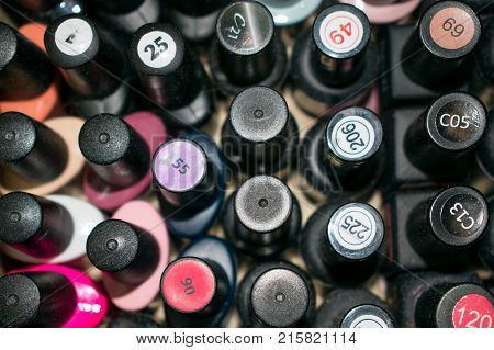 Fine art nail concept with a lot of bottles nail polish viewed from the top. Many color and black bottles of nail polish with numbers on the covers