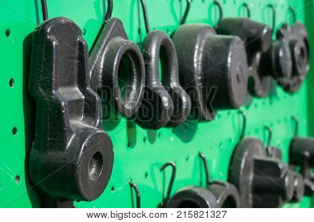 Black cast iron parts for agricultural machinery on a green background. Various Cast-iron industrial mechanical parts. Selective focus