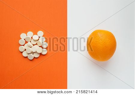 Vitamin C concept in minimalist style. Natural vitamin С in orange vs synthetic vitamin С in pills. Choice between natural and synthetic way of health care. Alternative medicine. Dietary supplement