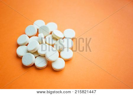 A pile of yellow ascorbic acid pills on an orange background. Synthetic Vitamin C. Prevention or treatment of the common cold. Dietary supplement