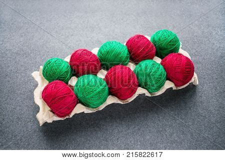 Balls of colored red and green yarn in a paper egg tray. Skeins of cotton yarn for knitting and creative needlework. Knitting as a kind of cozy needlework.