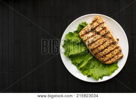 Chicken grilled steak on leaves slate on a white round plate on a black wooden background. Healthy food. Diet, fitness food. B-B-Q. Top View