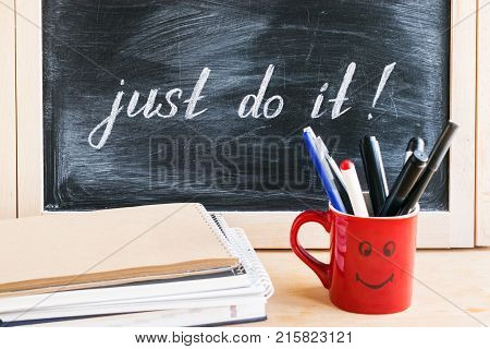 Lettering of phrase JUST DO IT on black chalkboard on a background of notepads and diary and a red cup with a cheerful smile. Procrastination motivation concept. Self-control and achieving the goal