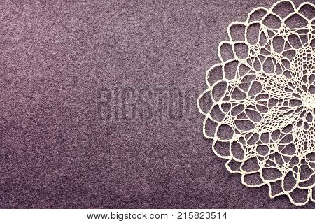 Beautiful delicate vintage background of crochet napkin on the dark felt canvas. Lace Vintage background with white crochet lace openwork napkin. Handmade embroidery sewing Knitted background