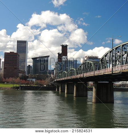 Downtown Portland Oregon with bridge across the Willamette River on a sunny partly cloudy day