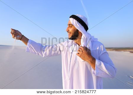 Young Arab guy who takes sand in hand and lifts it to smiling face and blows through fingers fine white grains of sand in bottomless desert on hot summer day. Swarthy, handsome Muslim with short dark hair dressed in kandura, long, spacious dress