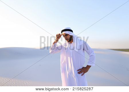 Portrait of tired Arab man, who holds head and feels migraine, tries to calm pain and massages whiskey, standing in middle of bottomless desert with snow-white sand on sunny summer day. Swarthy Muslim with short dark hair dressed in kandura, long, spaciou