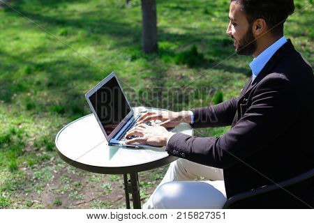 Gentleman sits on chair and telling story, wave hand. Actor has beard, black short hair and dimple on face. Concept of new interesting TV programs and work for actors talk shows.