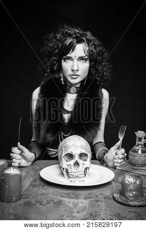 Wicked girl preparing for dinner with skull in her plate over dark background