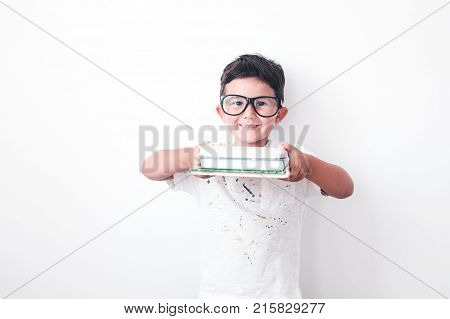 Back to school kid. Happy little boy with huge glasses holding books getting ready to kindergarten. portrait with white background.