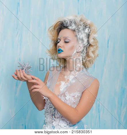 Close up portrait ice queen in the image of the Snow Queen. Beautiful girl with creative makeup in a transparent dress. The beauty of the face. Fashion, beauty.