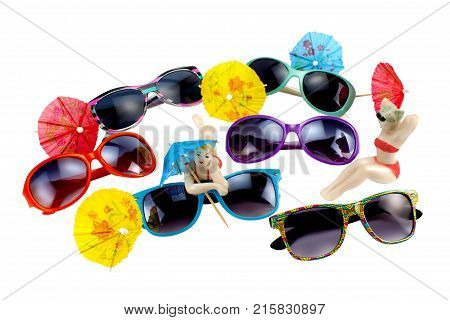 Sunglasses cocktail umbrellas and porcelain figurines of bathers on white background